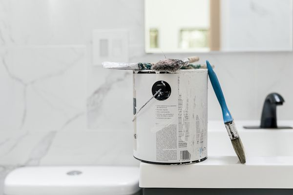 paint can and brushes in a bathroom
