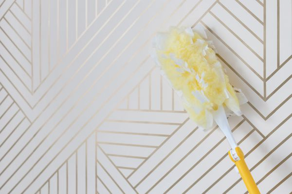 White and gold striped wallpaper cleaned with microfiber duster