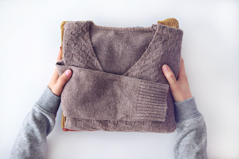 Midsection Of Woman's Hands Holding Sweaters