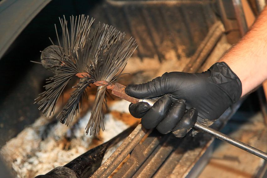 a hand holding a metal chimney sweep brush