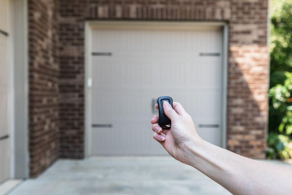 Garage door remote being pressed in front of tan garage door