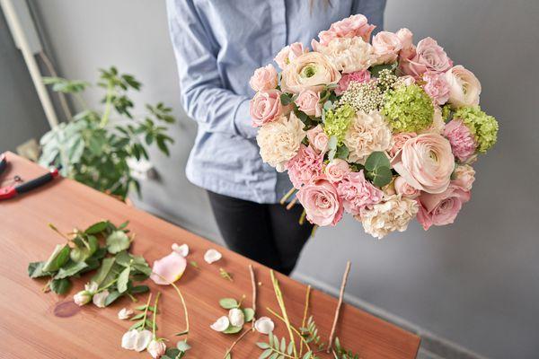 Woman florist creating beautiful bouquet in flower shop. Work in flower shop. Flowers delivery.
