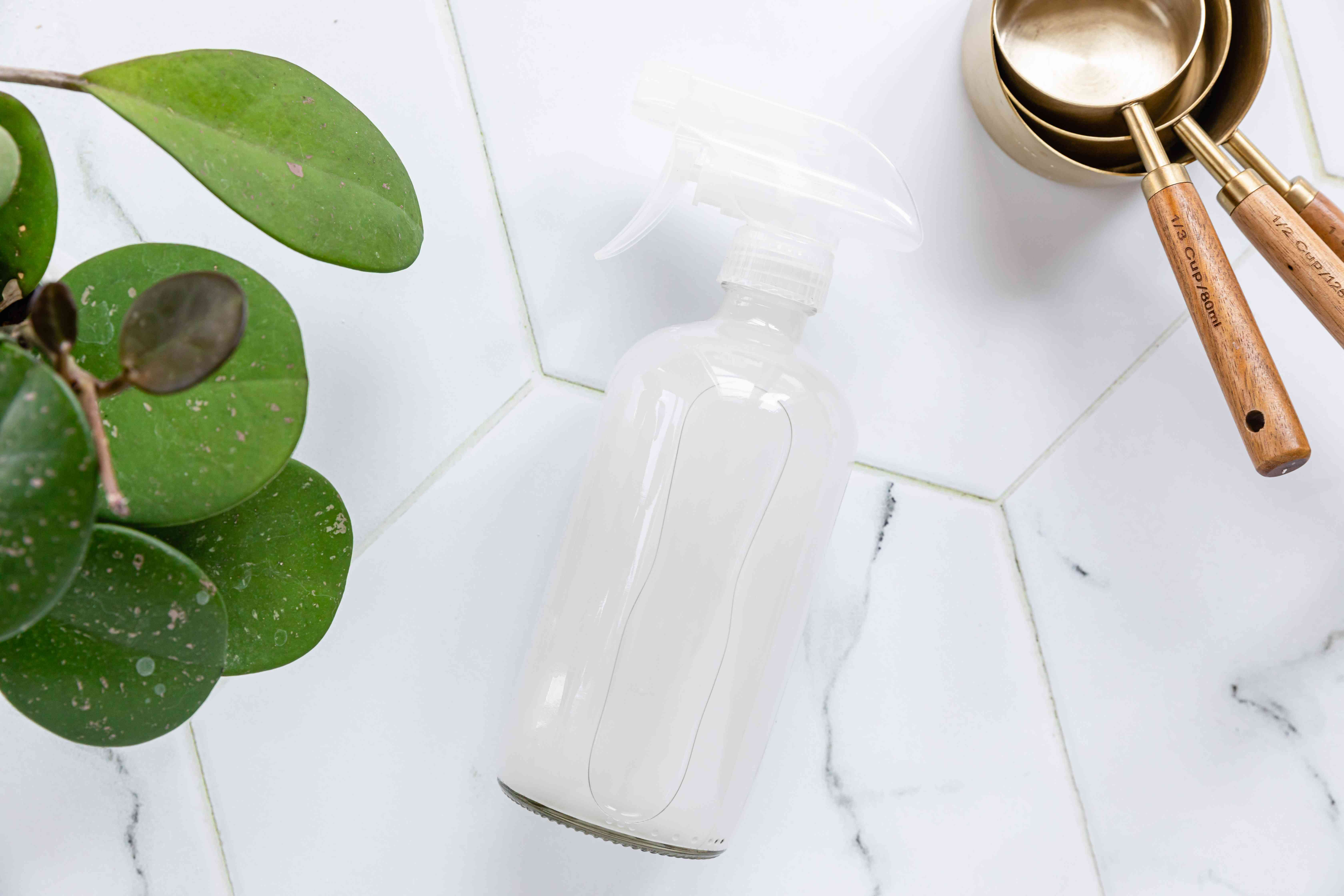 DIY laundry starch and sizing with glass spray bottle, metal measuring spoons and cold water next to houseplant