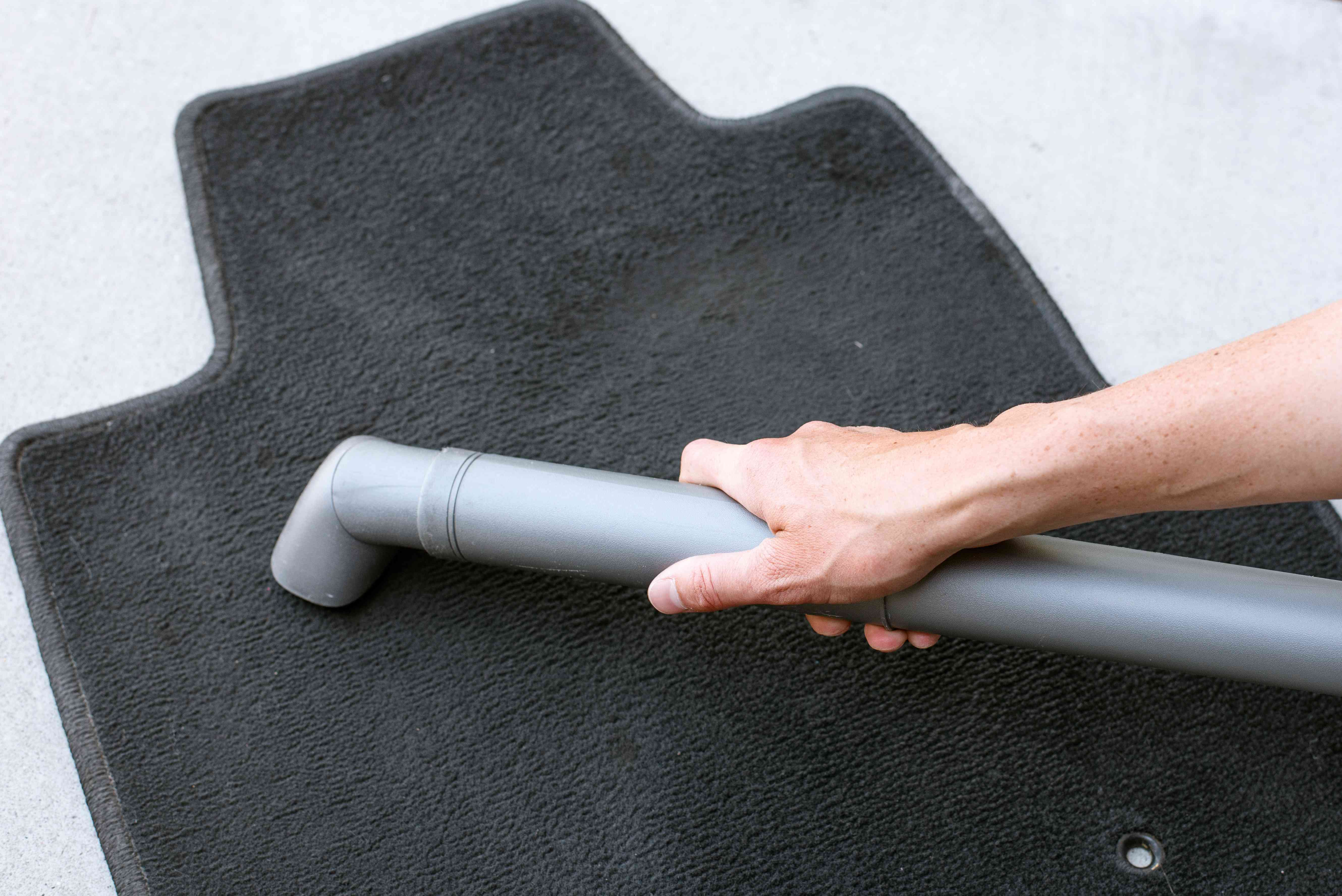 Black car mat being vacuumed while lying flat