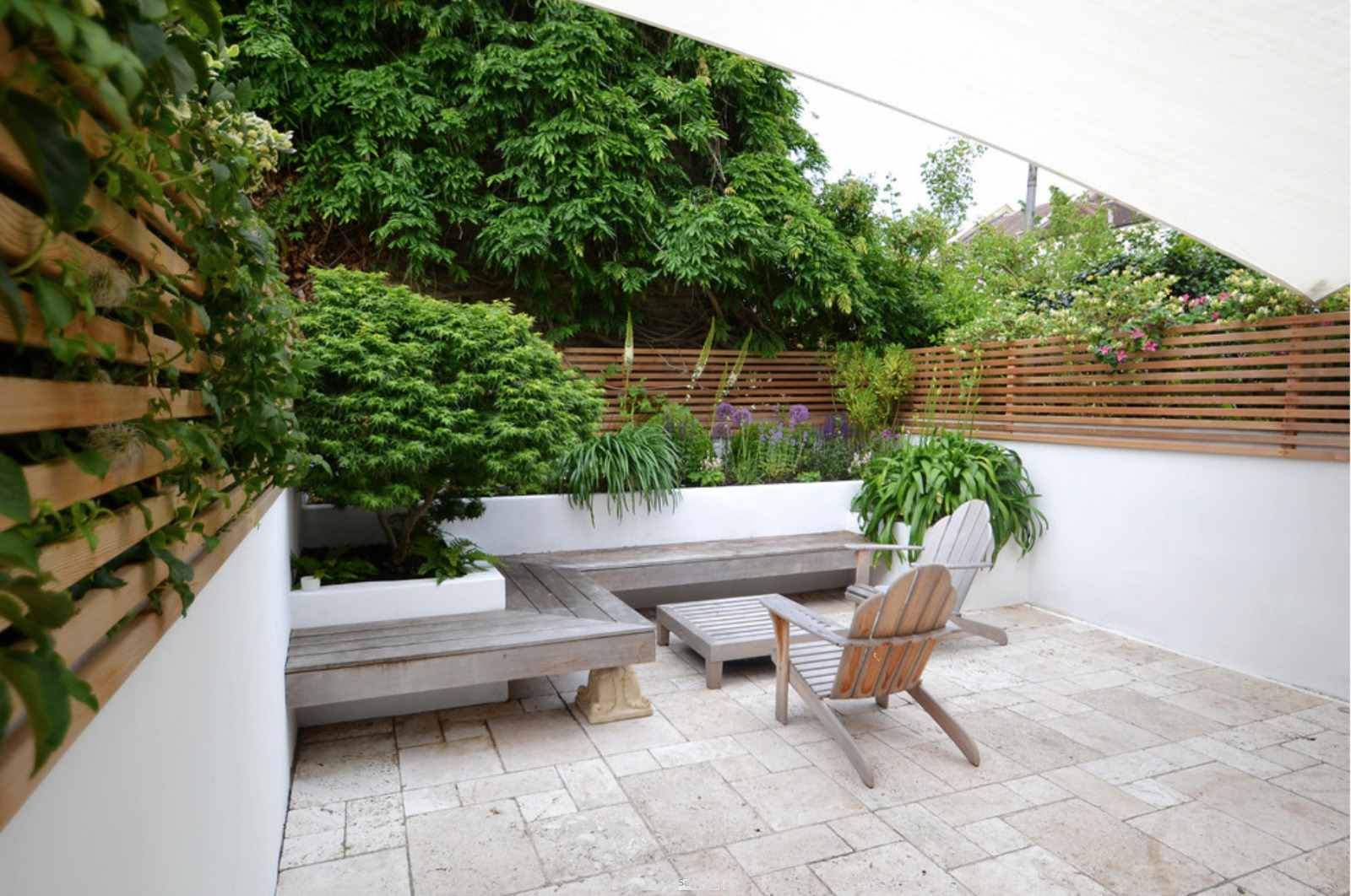 Living wall near wooden pallets along with bench and chair.