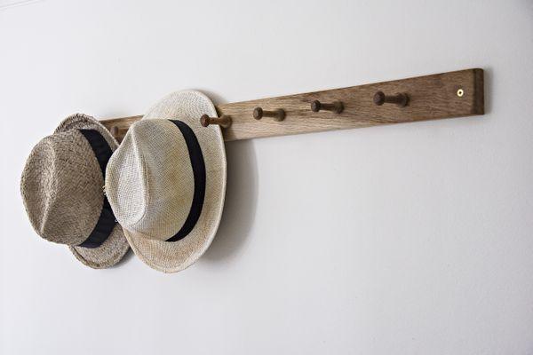Hats hanging on hook on wall in bathroom