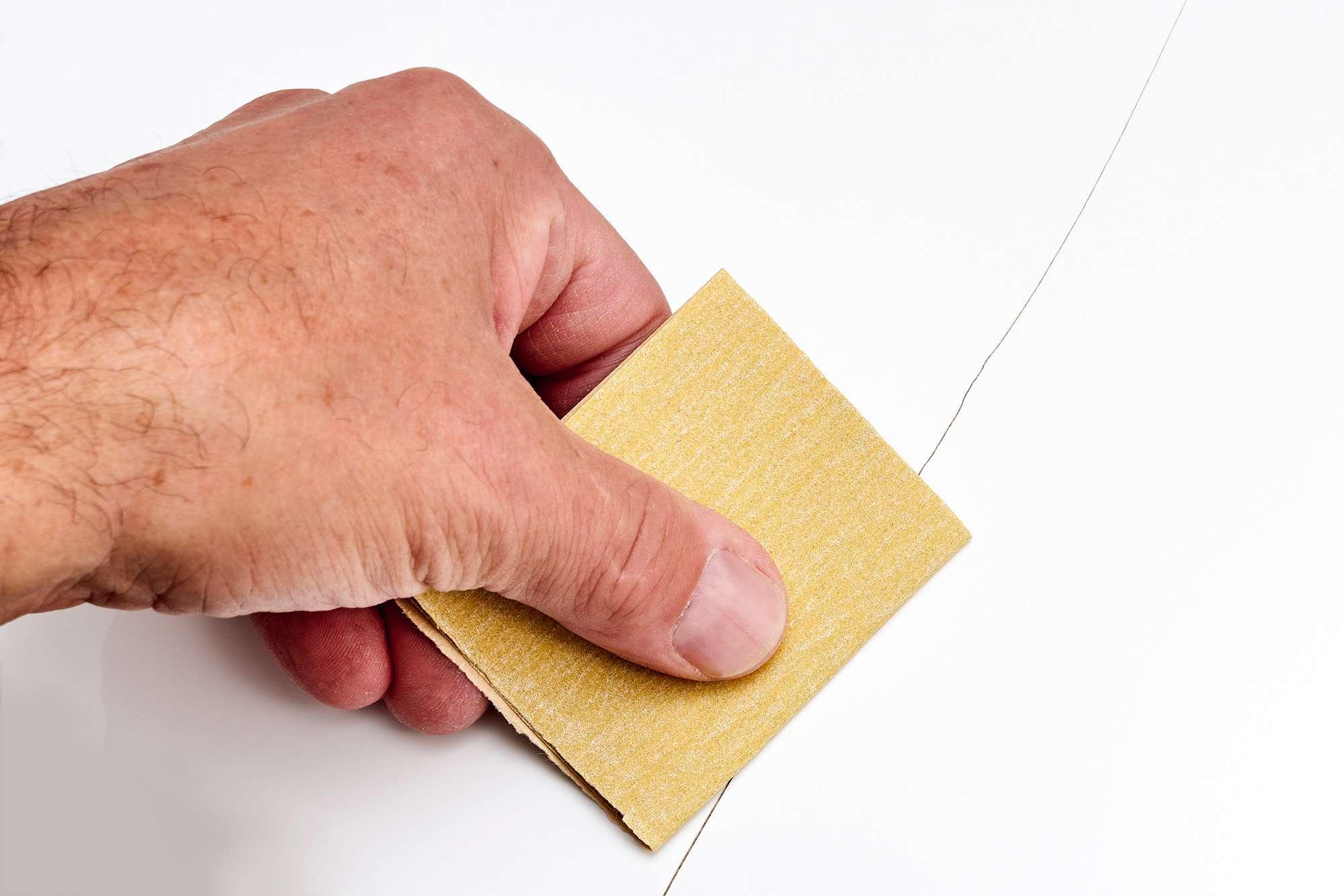 Sandpaper roughening hairline crack surface area on toilet bowl or tank