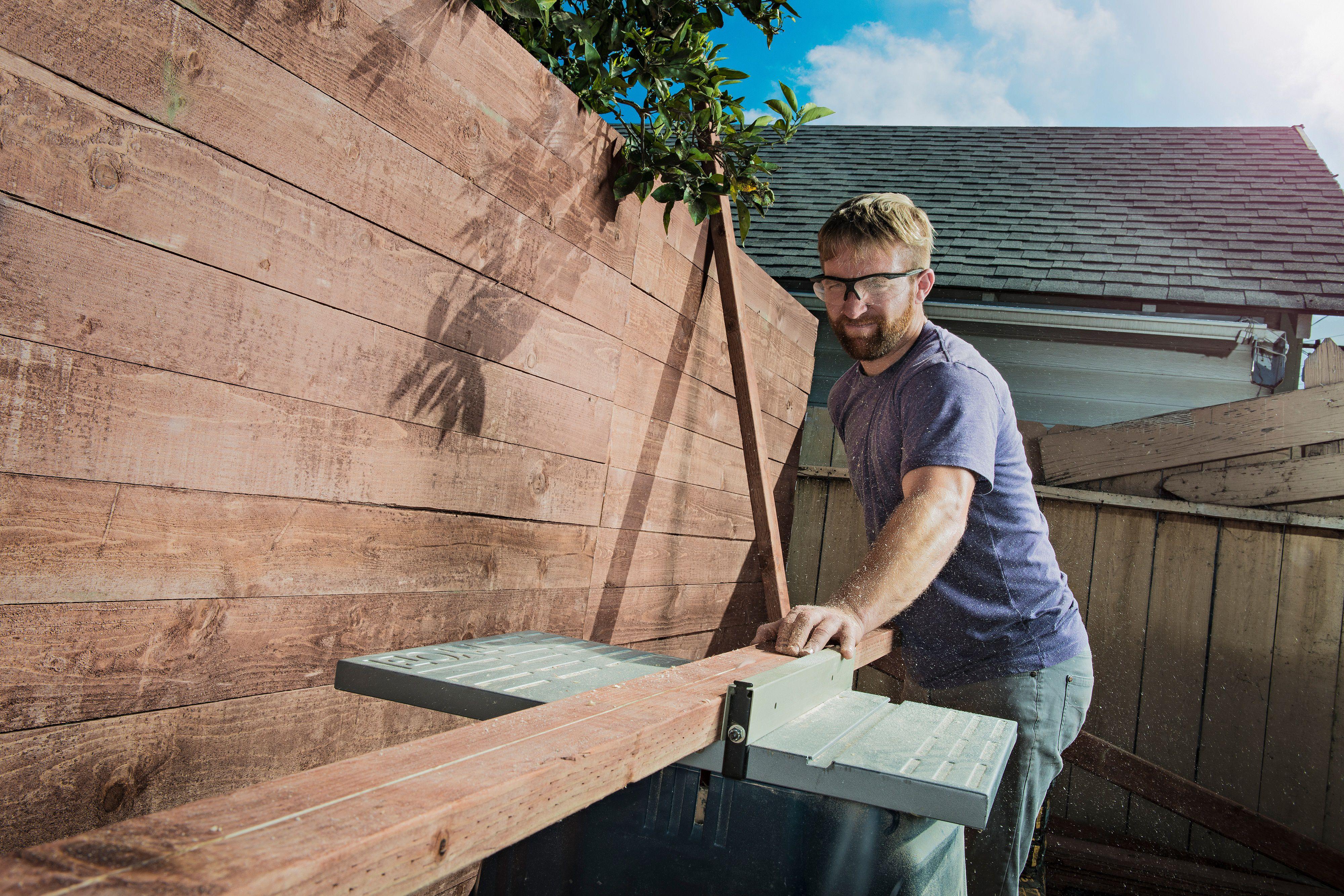 hombre construyendo cerca de madera