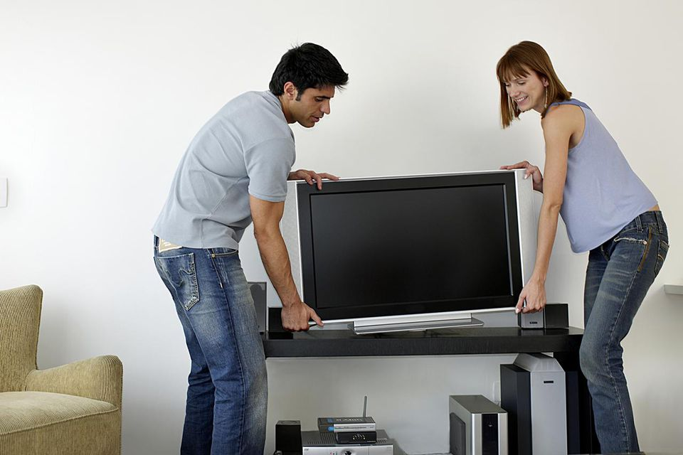 Couple holding flat screen television, side view