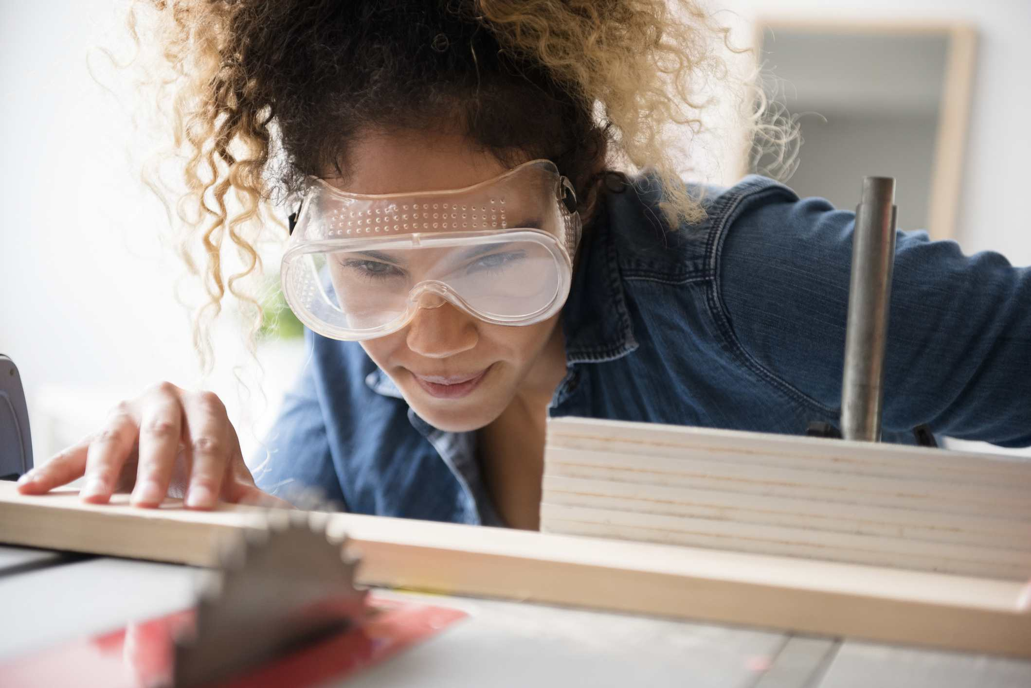 A woman using a table saw
