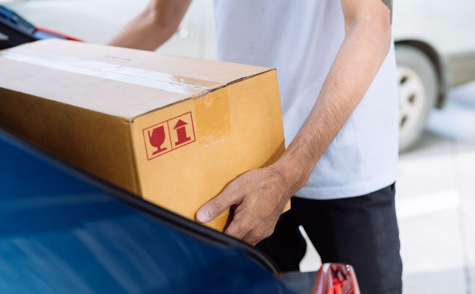 Delivery Man Carrying Cardboard Box For Sending To Receiver Customer By Transportation