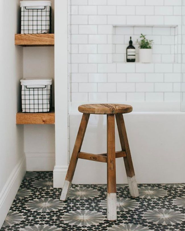 small bathroom with stool and storage containers on wooden shelf.