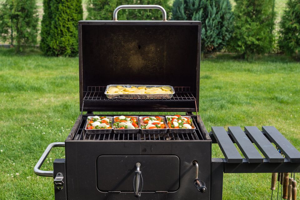 Opened Grill With Food On Trays Inside, Standing On The Backyard Garden On The Lawn