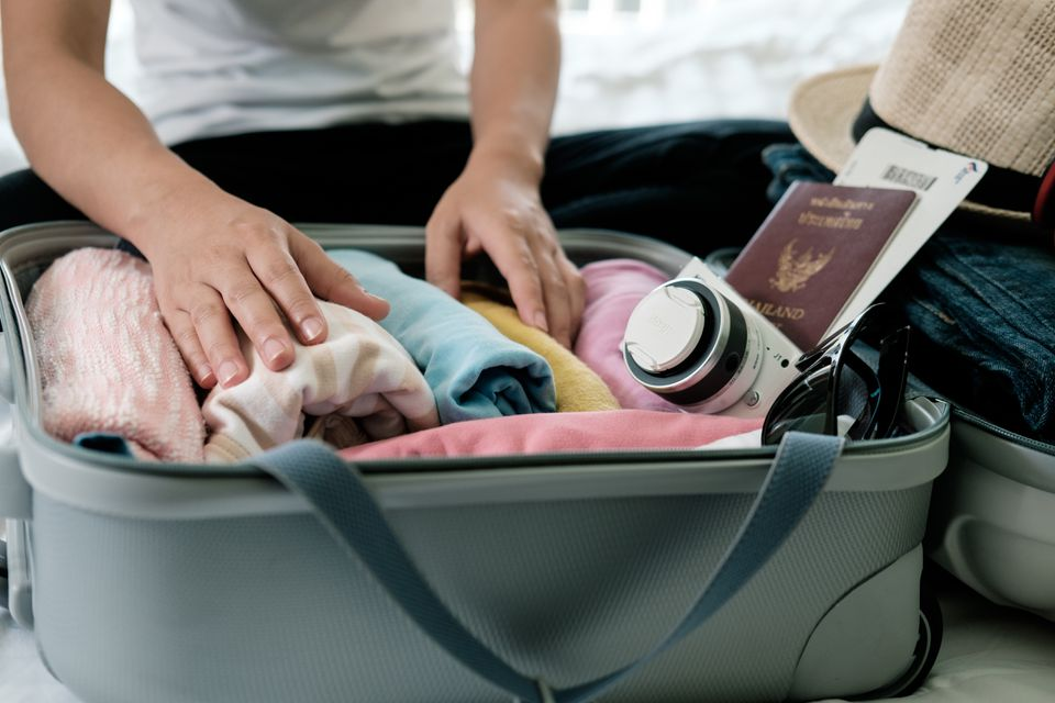 Person packing for an overseas trip with passport