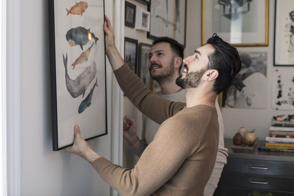 Gay couple hanging painting on wall at home