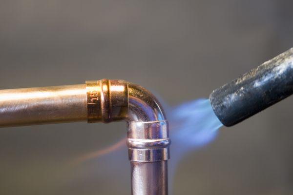 Torch solders copper pipe