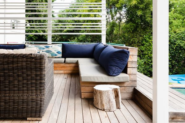 Backyard deck with white and blue cushions and stump in front