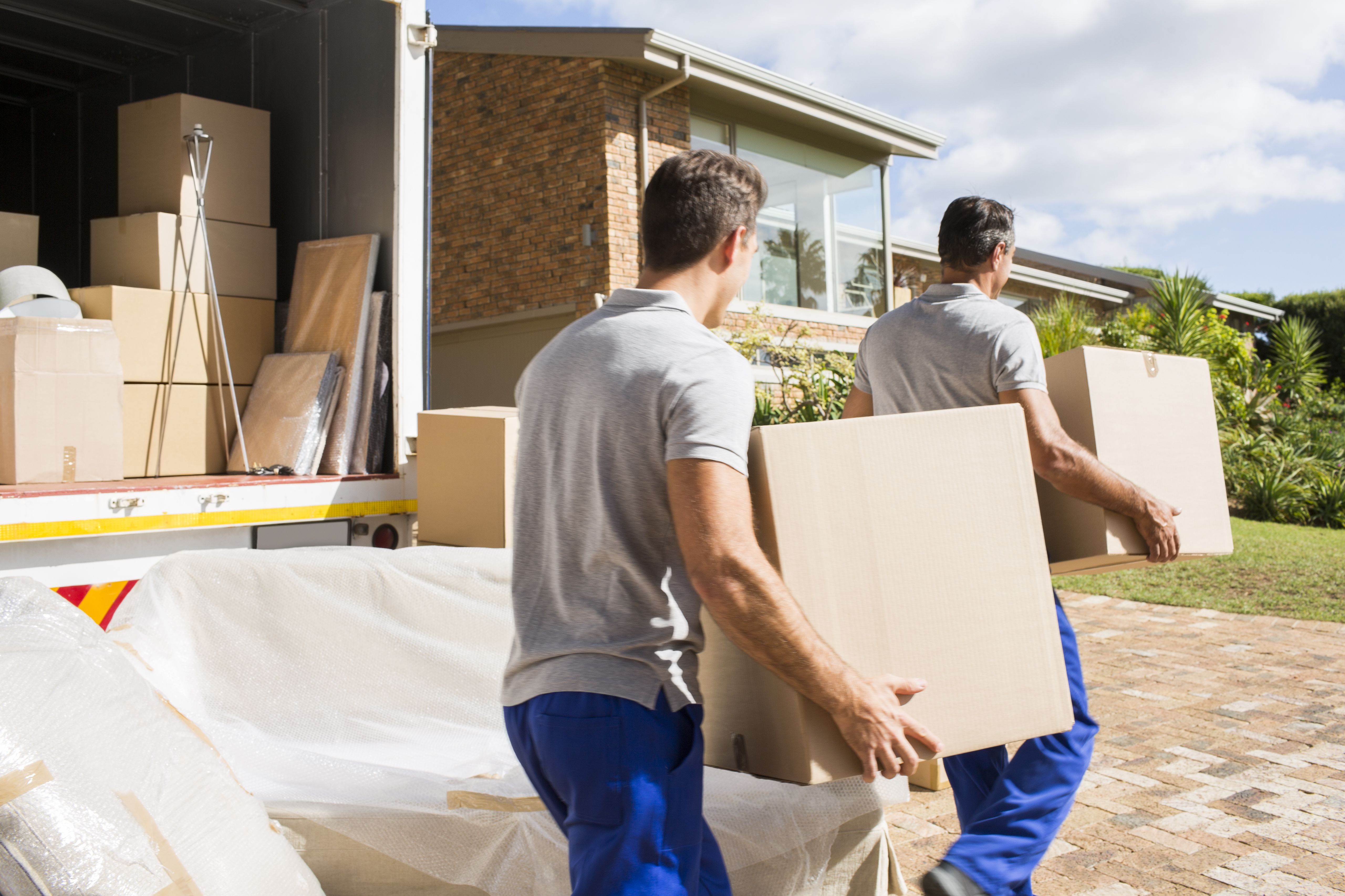 Movers carrying boxes in new house
