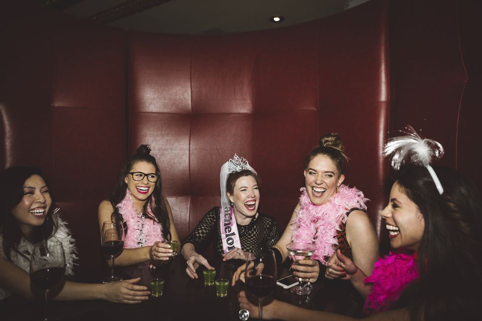 Playful young female friends drinking in a bar for a bachelorette party