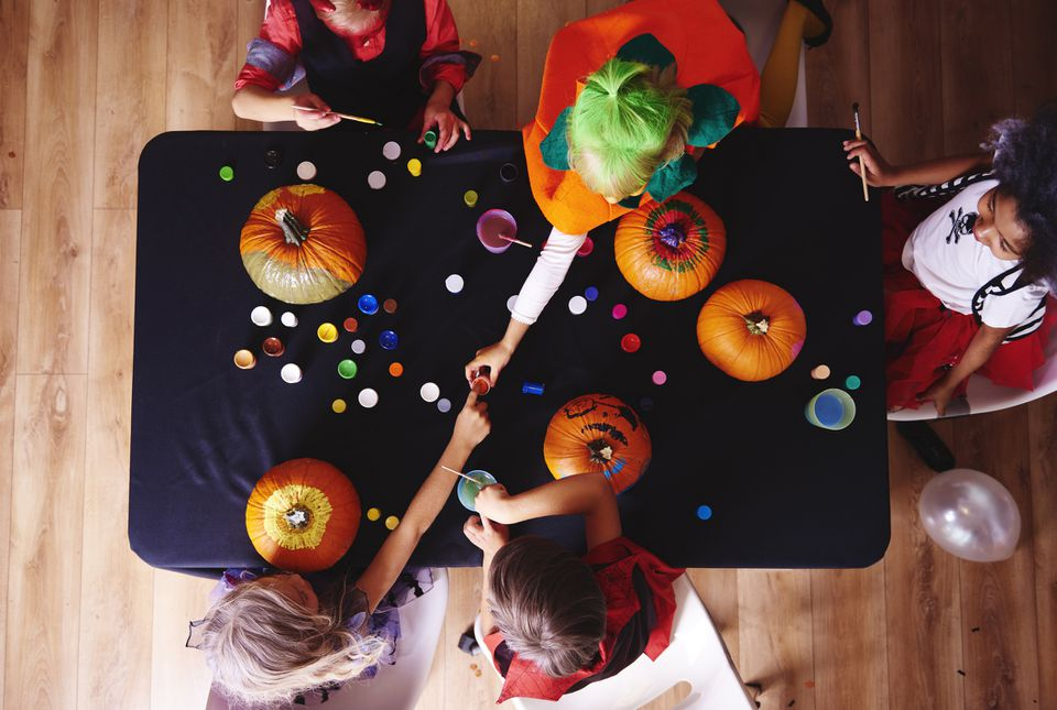 Kids in costumes decorating pumpkins