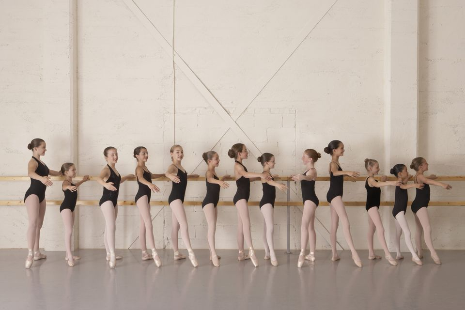 Girls in ballet class, holding bar in ballet pose, side view