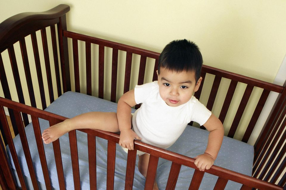 Toddler boy (18-24 months) getting out of crib, elevated view