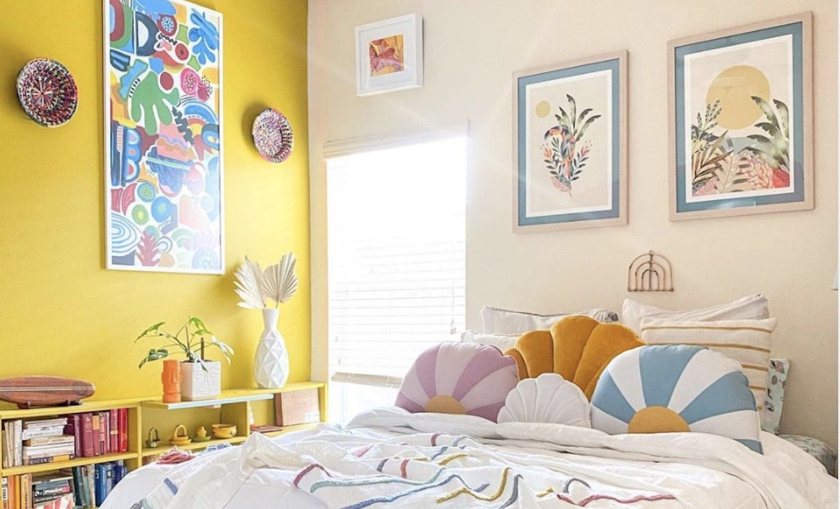 bedroom with bright yellow accent wall, prints hanging on wall,