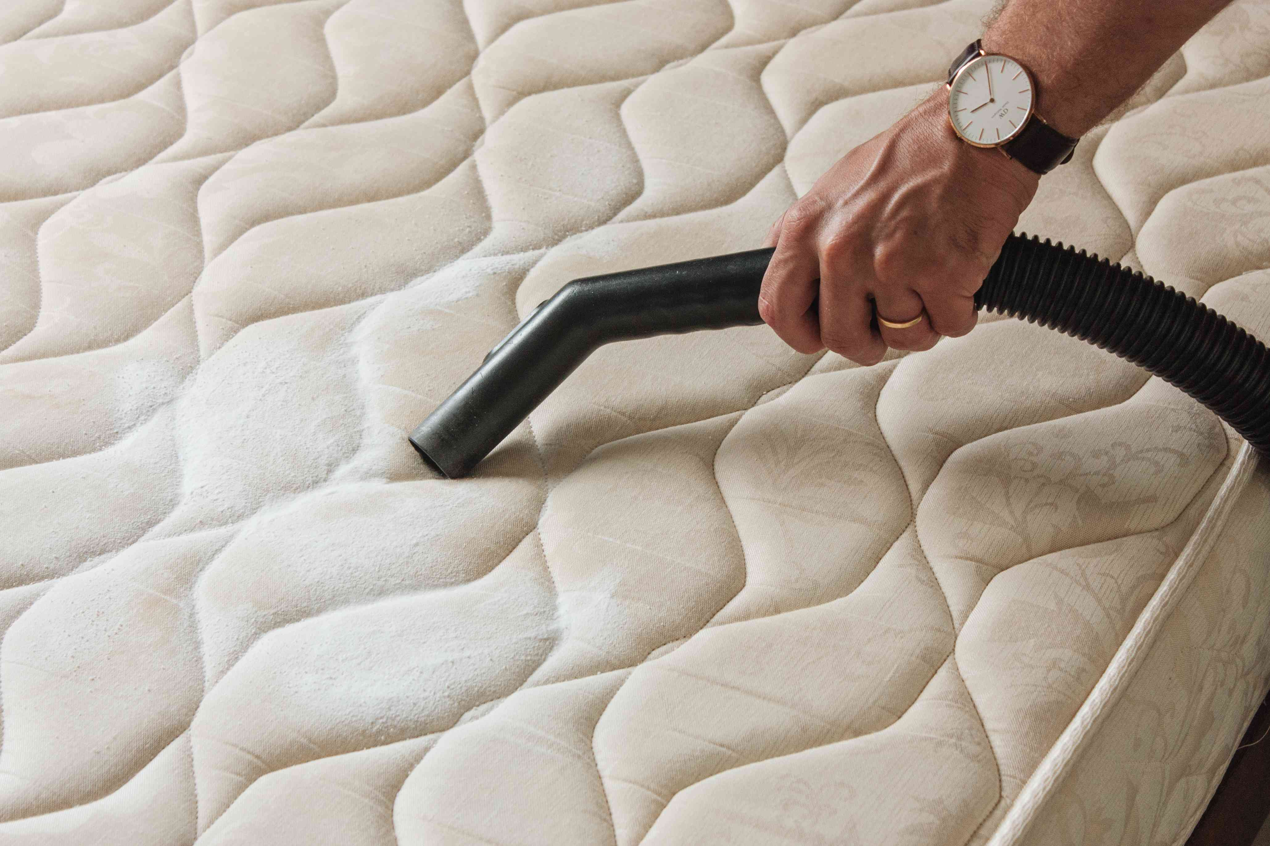 person vacuuming baking soda off of a mattress
