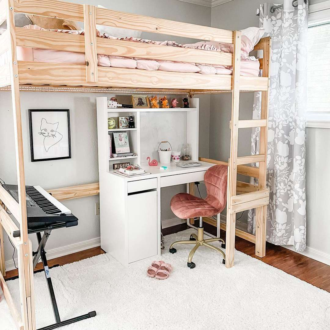A loft bed in a kid's room with a desk, chair, and keyboard at the bottom and bed on top.