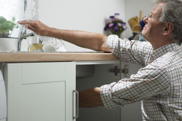 A man attempting to fix a sink in a kitchen