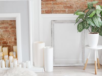 Light white interior photographed with natural light. Flat brick wall with fake fireplace, candles, roll of papers and house plant on the table