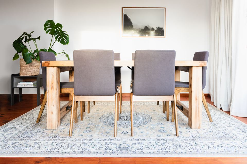 Light colored patterned rug underneath dining room table