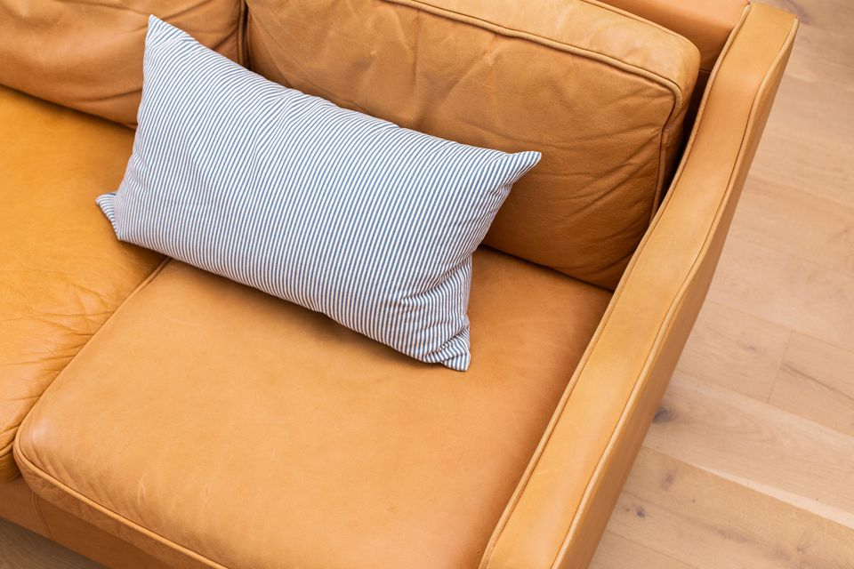 Brown leather couch with white striped pillow on cushions