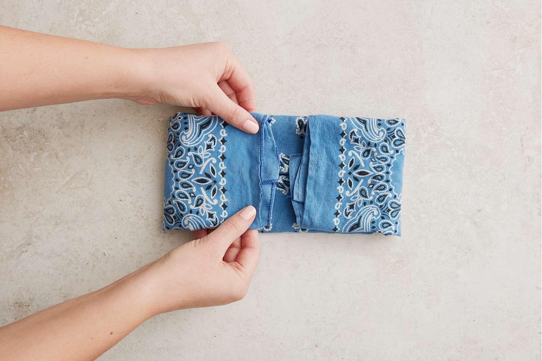 Hands folding bandana inwards