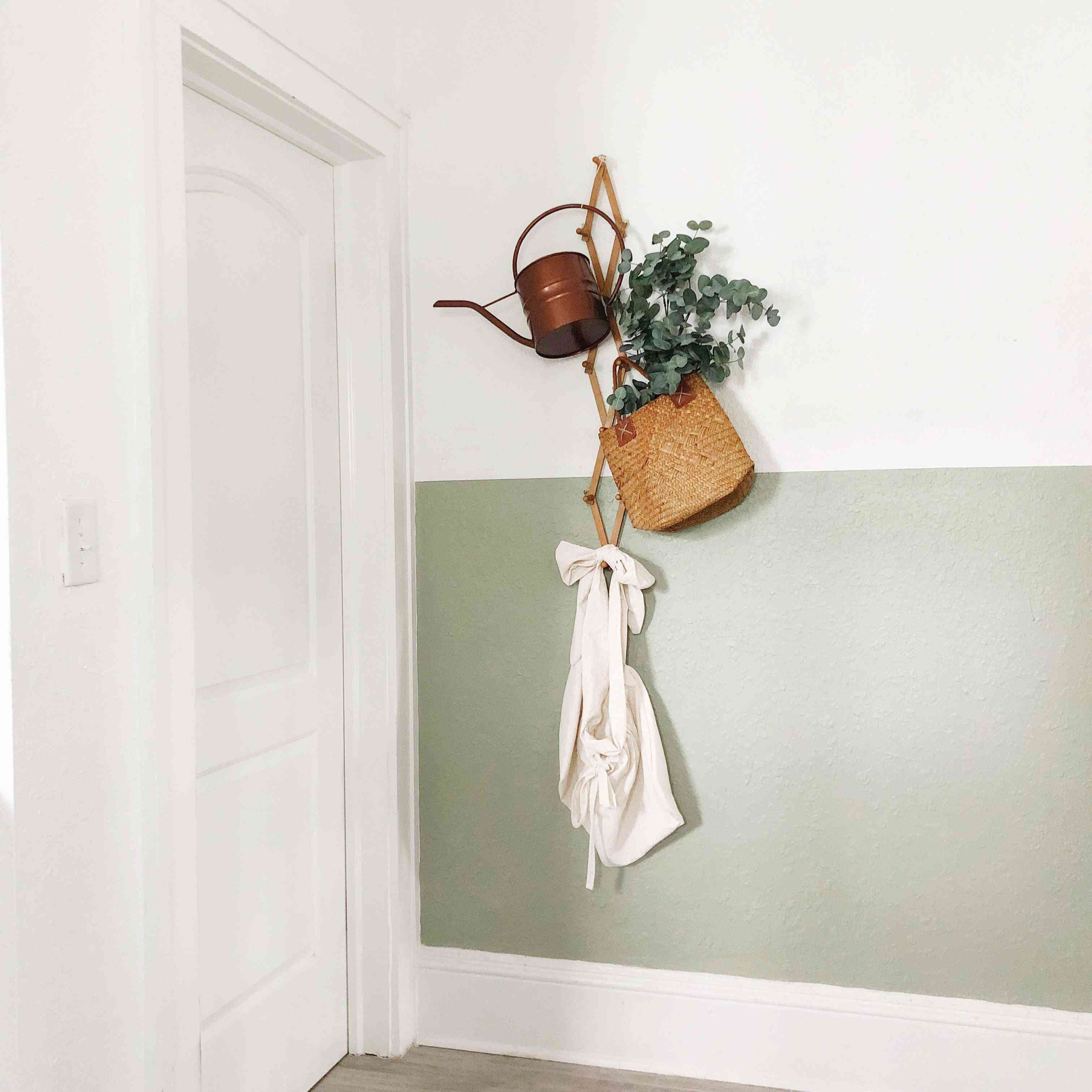Half-painted wall with plant decor by home designer Jessica Smith