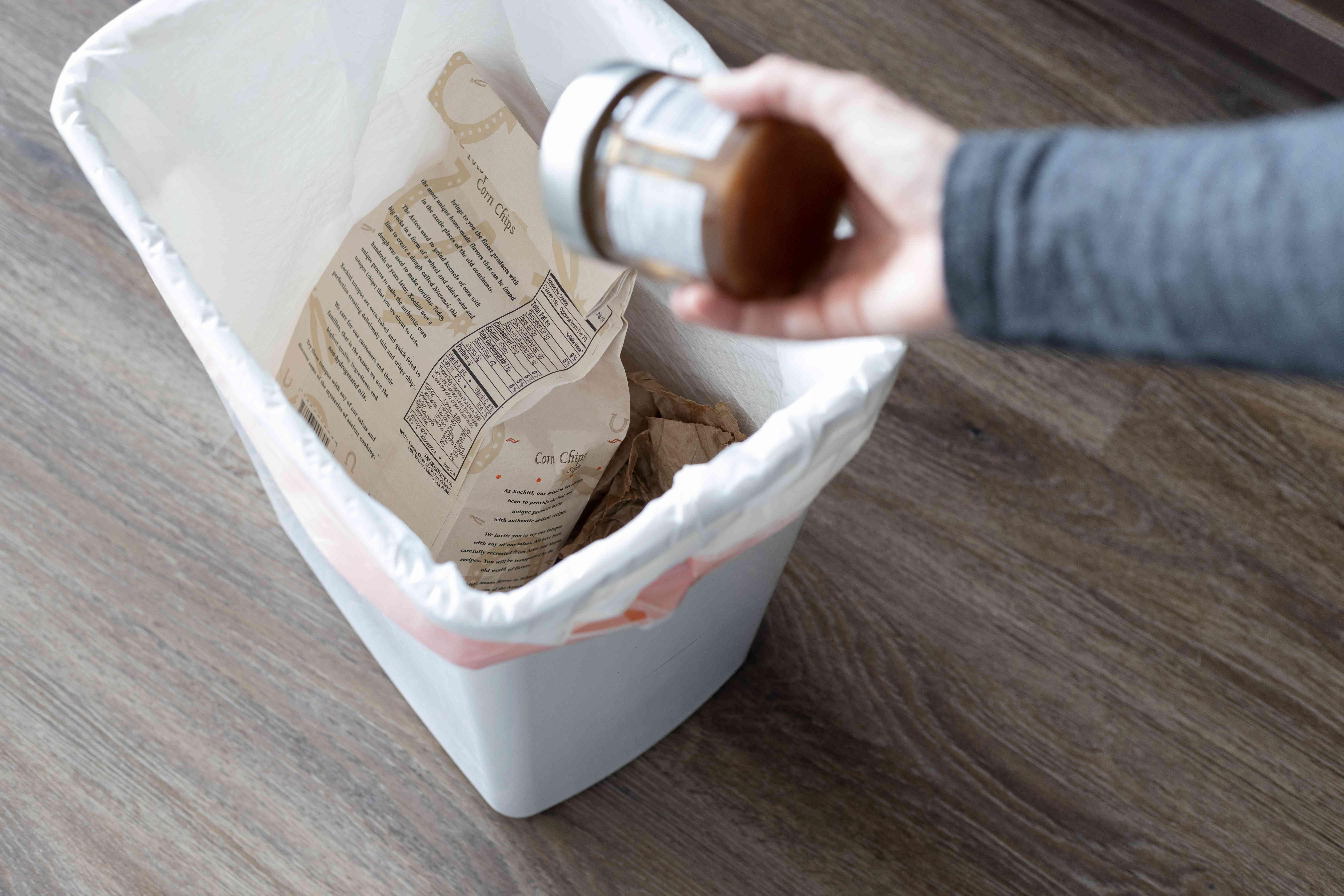 Kitchen items thrown into garbage bin by hand
