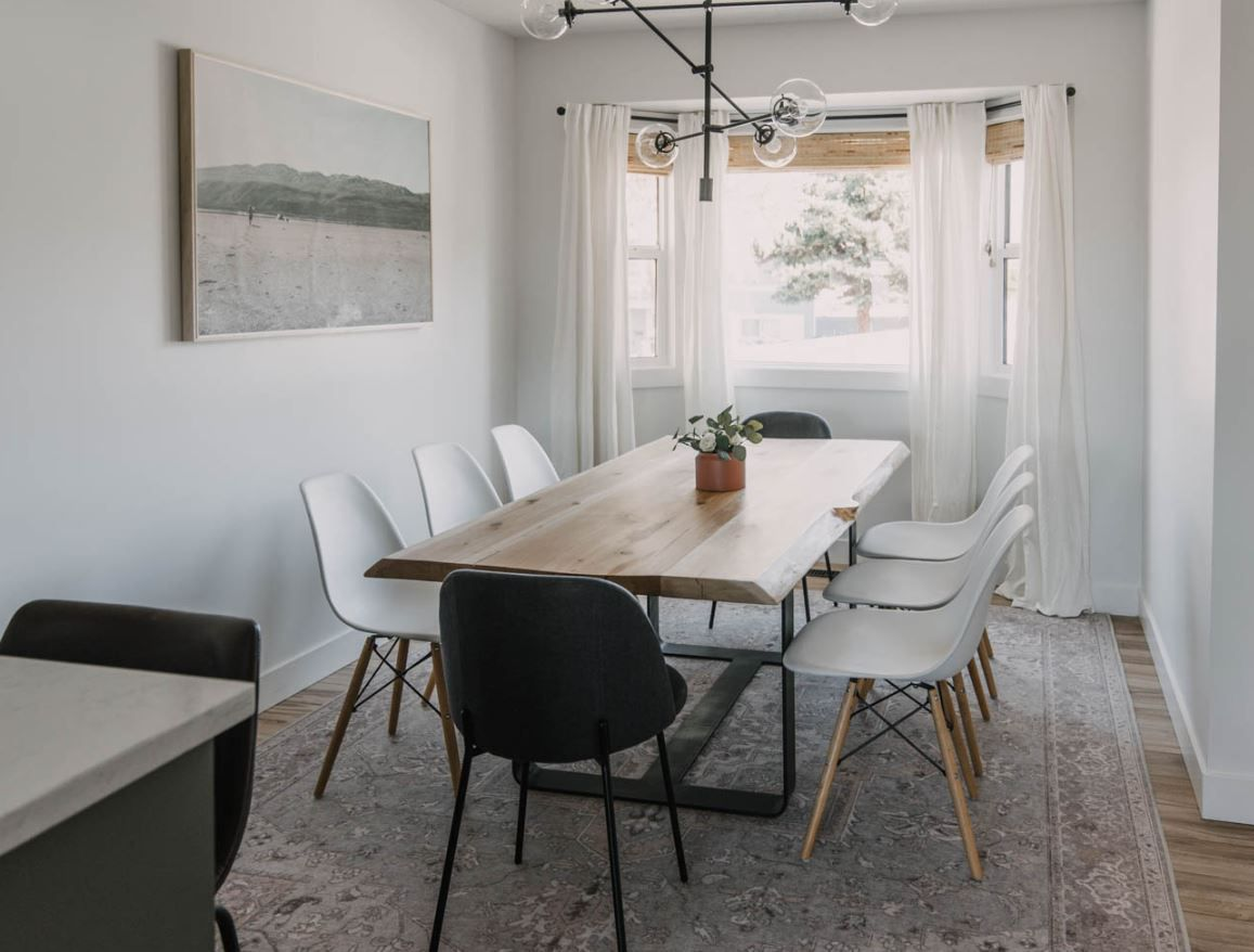 Modern dining room after makeover, with large print on wall and black and white seating.
