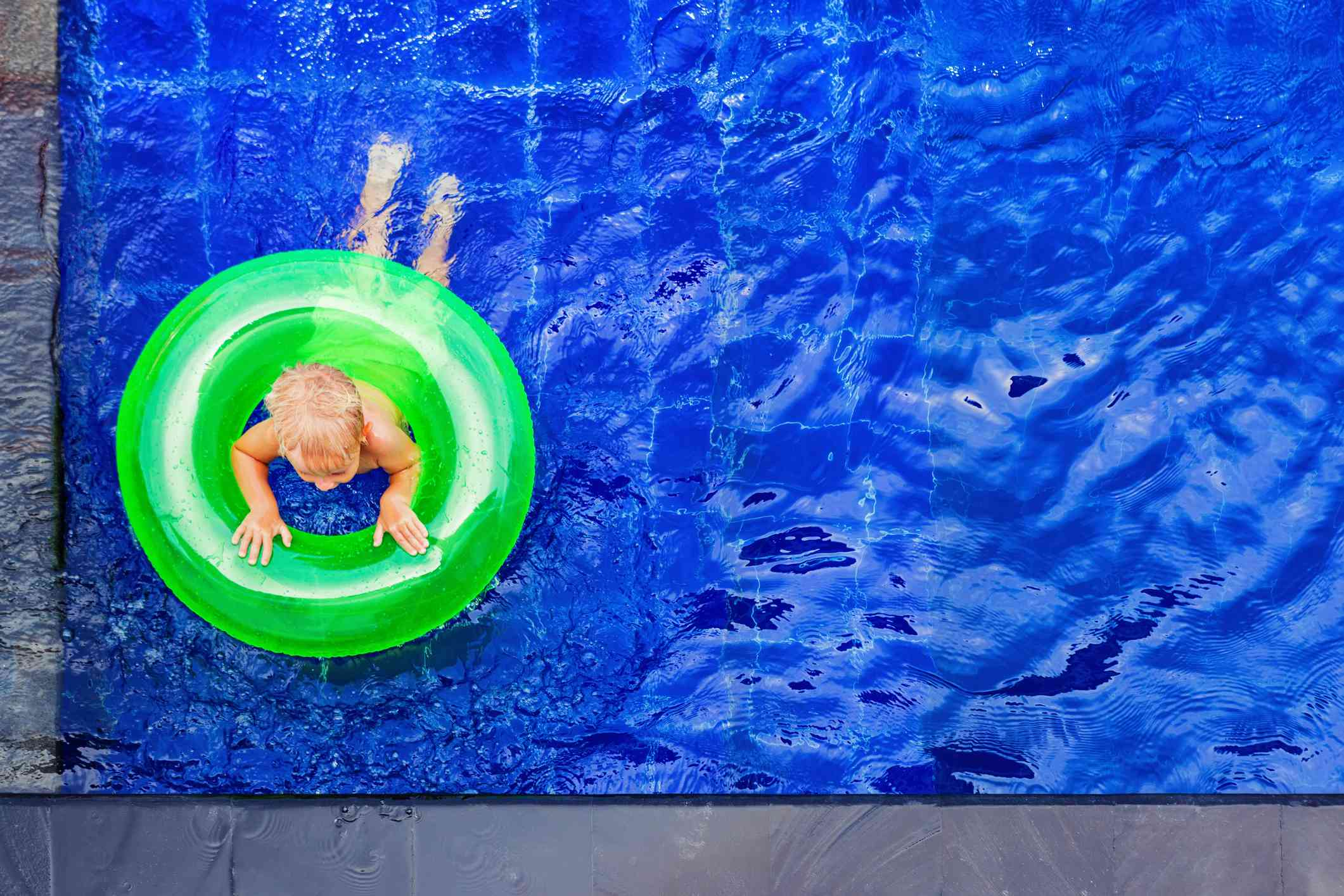 Happy child have fun on inflatable ring in swimming pool