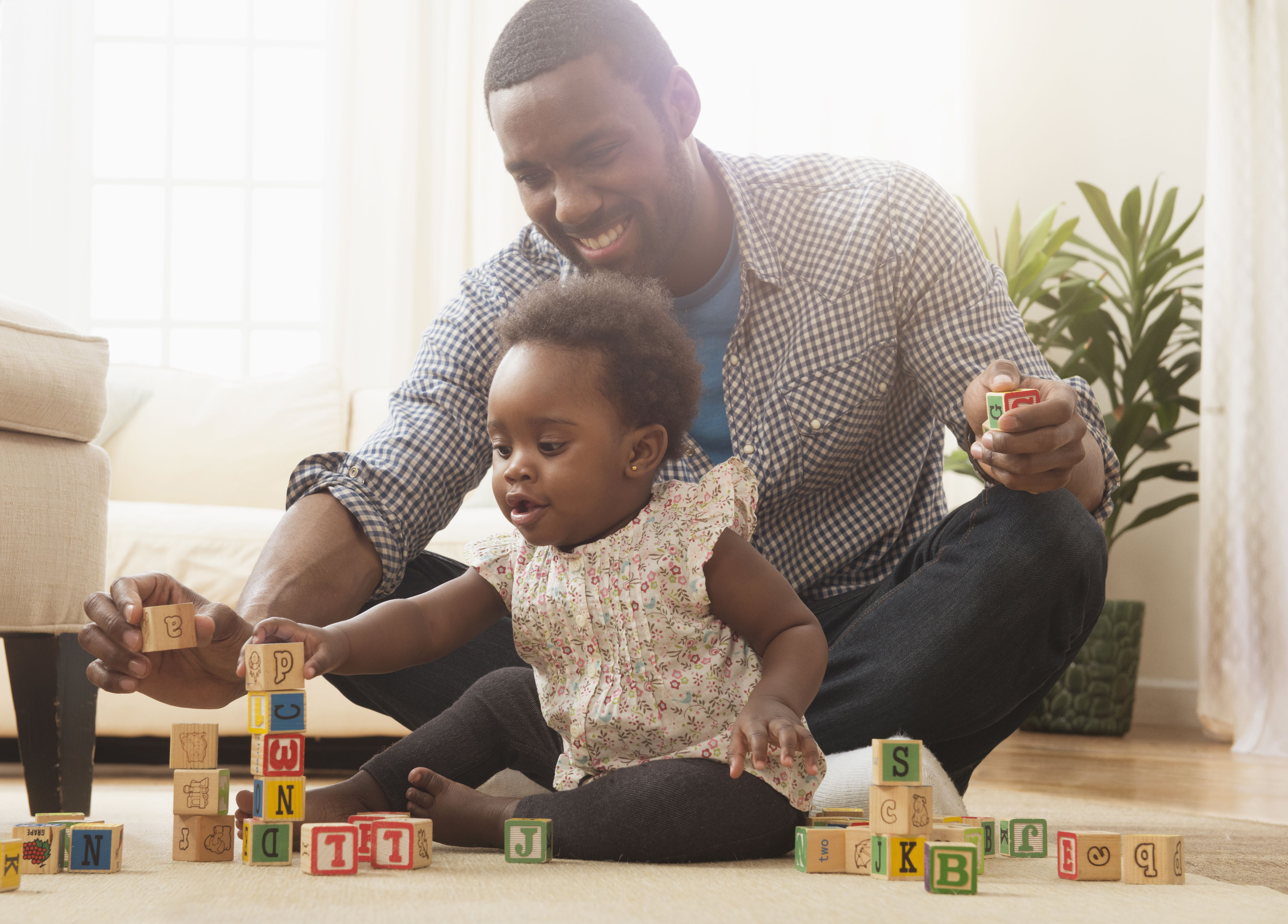 Father and baby daughter playing with wooden blocks