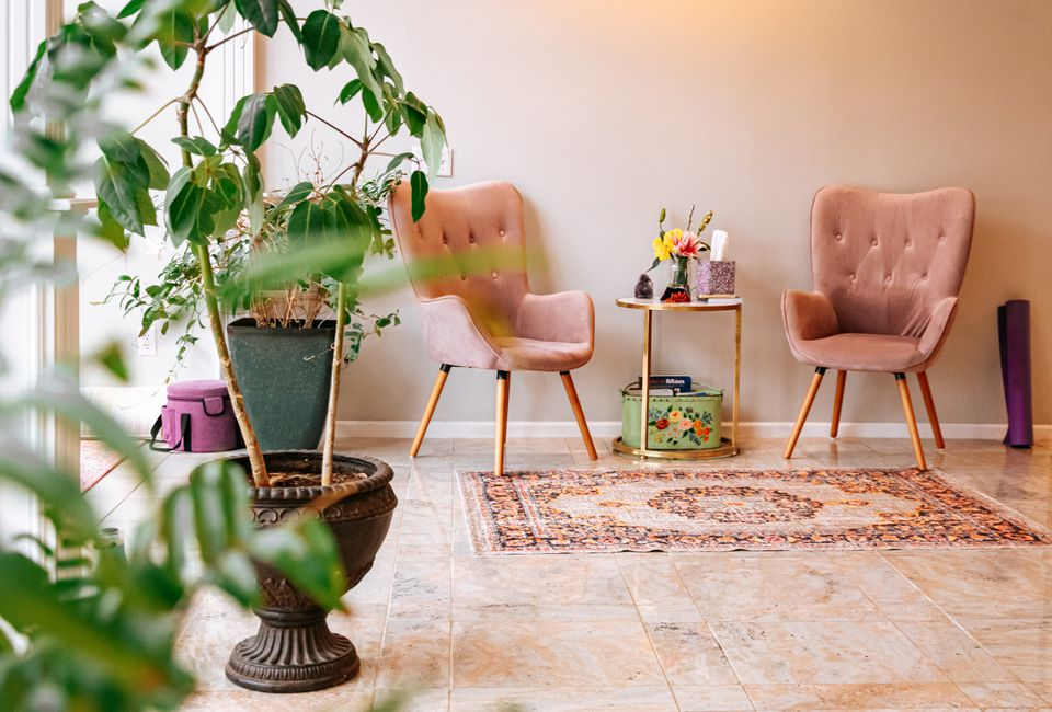 home interior with two pink chairs, a rug, and plants
