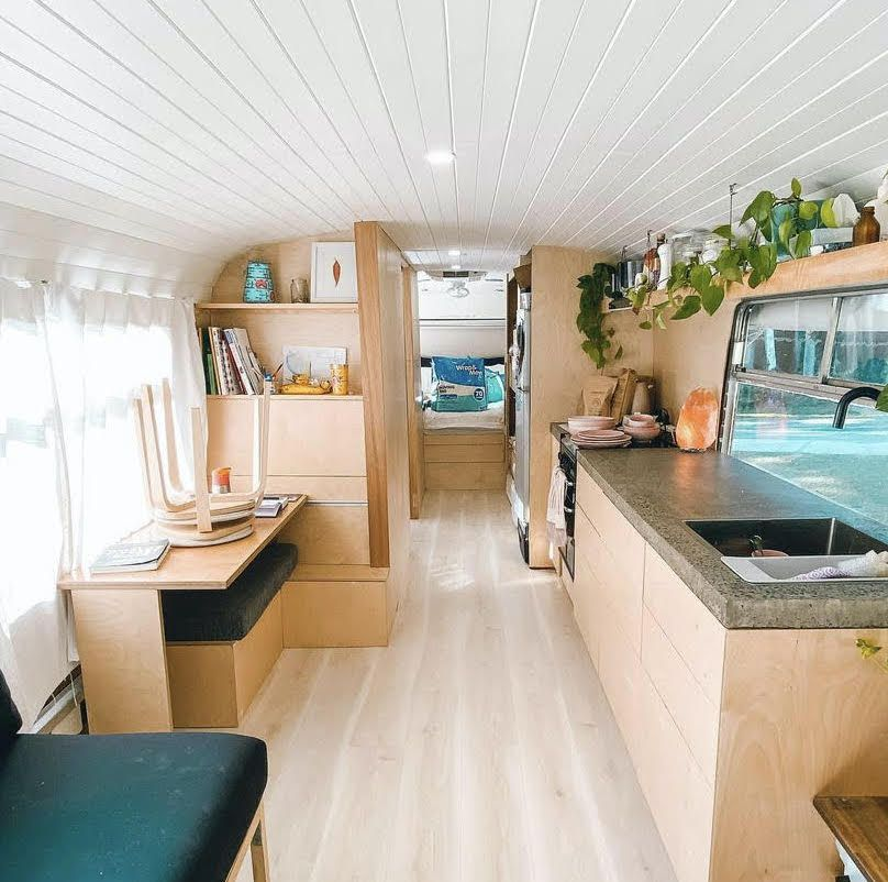 A converted schoolbus kitchen with clean lines and a white ceiling