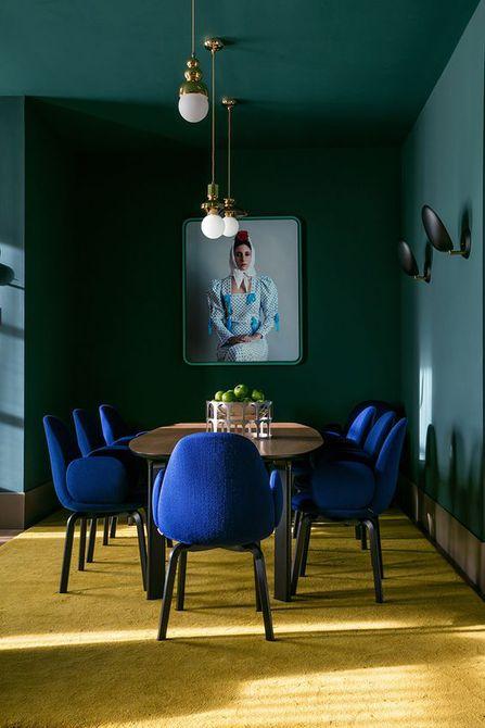 Sillas azules y pared en el comedor  , estilo ecléctico en el comedor