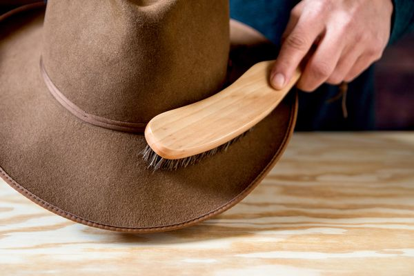 Someone cleaning a brown felt hat