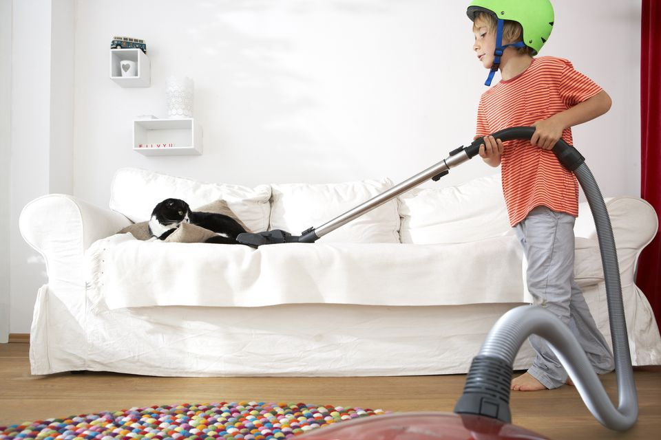 boy vacuuming couch