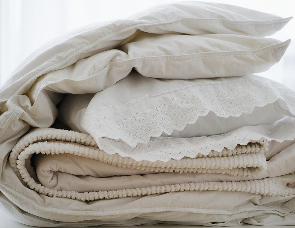 A down cover wrapped around sheets and a pillow