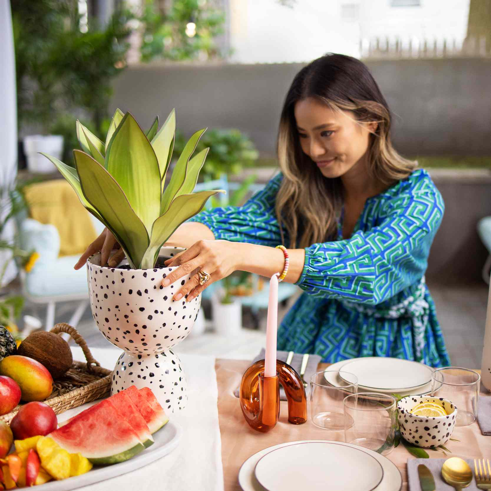 Jamie Chung arranges a planter on her backyard dining table