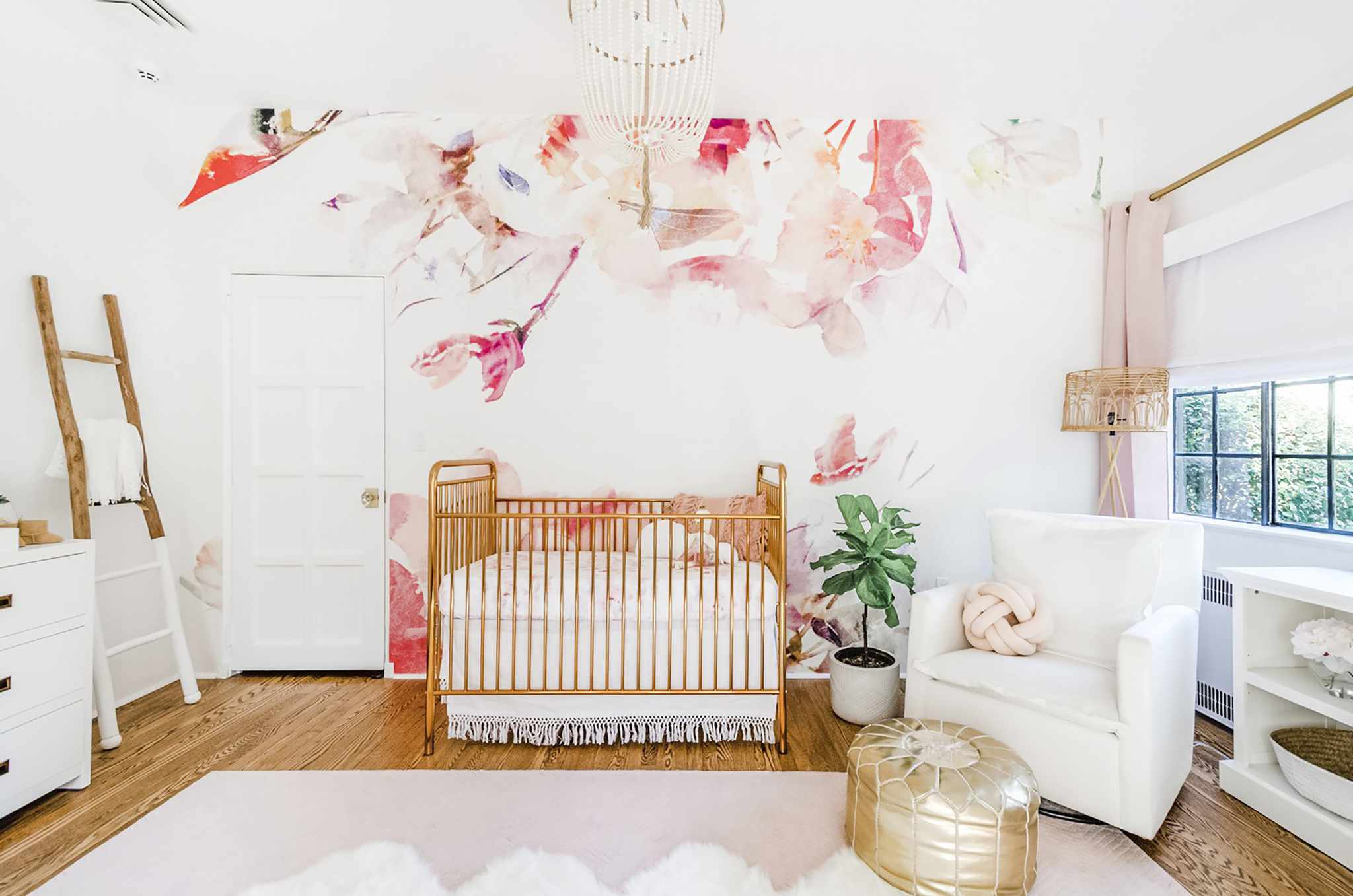 a pink and coral wallpaper mural with flowers used in a white nursery