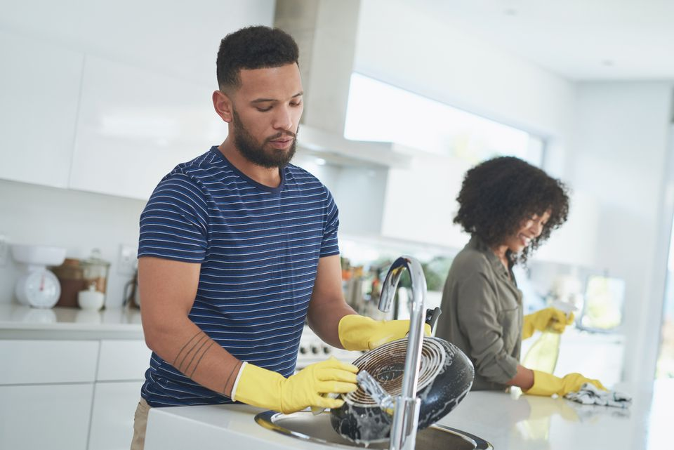 Couple cleaning kitchen together