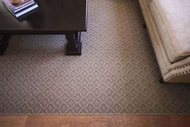 Patterned broadloom in greige color made into area rug.