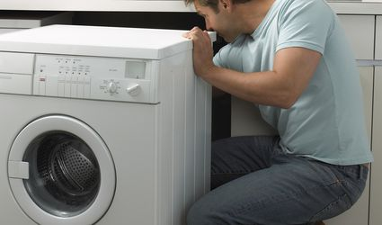 Person pulling out a clothes washer to determine what's wrong.